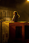 © Joel Goodman - 07973 332324 . 17 November 2013 . Oldham , UK . A girl sits on an Oldham Evening Chronicle box on the street to get a view of the stage from behind screened barriers . The Christmas lights are turned on in Oldham Town Centre . Photo credit : Joel Goodman