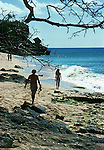 Couple walking along the rocky beach the man is carrying a speargun, Barbados, Caribbean,