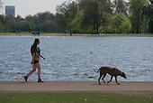 Woman walking a dog, Kensington Gardens, London.