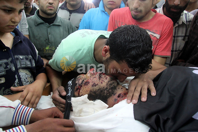 A Palestinian relative kisses the body of Haitham Al-Mes-hal, who relatives said belonged to a militant Jihadist Salafi organisation, during his funeral at a mosque in Gaza City April 30, 2013. Israel on Tuesday launched its first targeted attack on a militant in Gaza since a war in November, killing the Palestinian jihadist in an air strike that put further strain on a five-month-old ceasefire. Photo by Ezz al-Zanoon