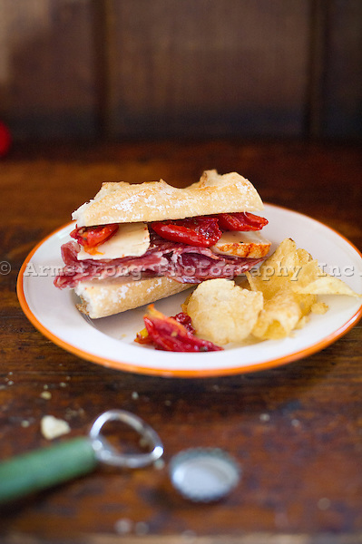 A baguette sandwich with salami, havarti cheese, roasted red peppers, and sun-dried tomatoes. On a plate with potato chips. Bottle cap and bottle opener in foreground