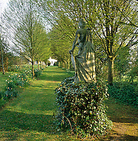 Looking past a statue of a Roman warrior up an avenue of hornbeams towards the house