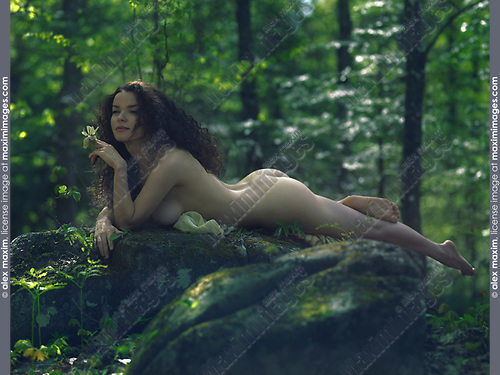 Sensual artistic nude portrait of a beautiful sexy young woman with a flower lying naked on a rock in a deep green forest with a dreamy thoughtful expression