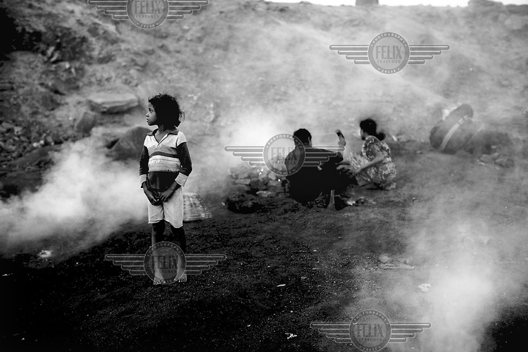 A child stands between the burning mounds of coal scavenged from the surrounding open cast mines and then processed into coke and charcoal. On the margins of such mines small communities of people make a precarious living scavenging coal and selling charcoal and coke they make from it. Below ground permanent fires burn, fuelled by seams of coal. The ground can be too hot to walk on and there is an ever present danger that houses will collapse into the vast underground caverns that are left unfilled after mining operations have ended.