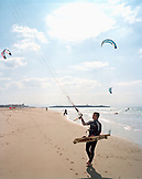 SPAIN, Andalusia, Tarifa, man kiteboarding and holding windsurf at beach