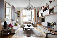 A spacious sitting room with a bay window with shutters. The room is furnished with an opulent chandelier, a coffee table set on a rug and two sofas.