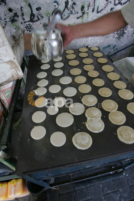 A Palestinian baker makes small traditional pancakes on the first day of the holy month of Ramadan in Rafah in the southern Gaza Strip on August 11,2010. Muslims all over the world fast from dawn to dusk during the holy month of Ramadan in the ninth month of Islamic calendar as they abstain from eating, drinking and having sex during the fasting period. Photo by Khaled Khaled