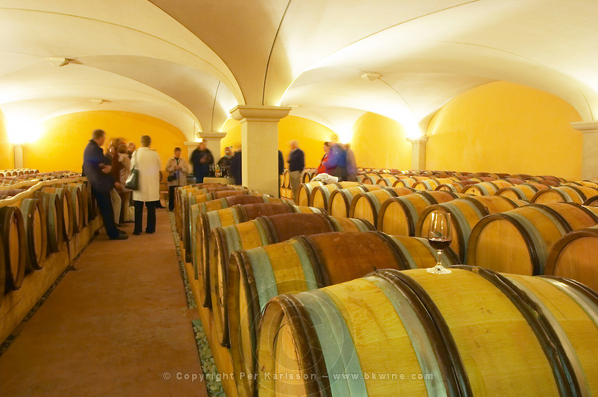 Visitors blurred in the barrel aging cellars with vaulted ceiling. A glass of wine on top of a barrel in the foreground. Domaine Gilles Robin, Les Chassis, Mercurol, Drome, Drôme, France, Europe