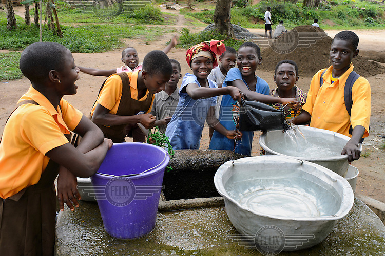 Children fetching water for their households at the end of the school day from a central well in the village of Annto.