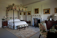 An Alexander Peter four-poster bed, its canopy decorated with fine carving, is one of eight in the house