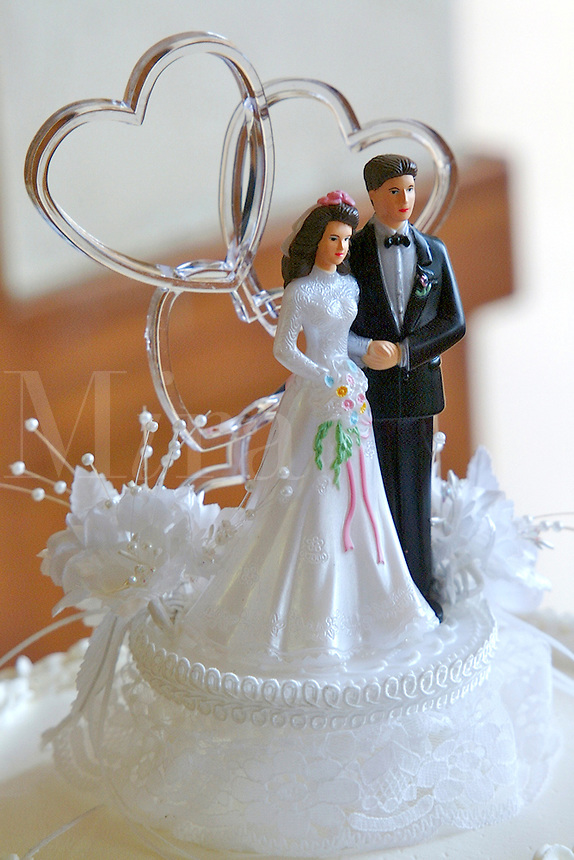 A bride and groom traditional wedding cake topper is on top of a white wedding cake.