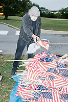 A man adds a flag to the pile as flags are gathered together for disposal in a flag retirement ceremony in Belmont, Massachusetts, USA, on Sat. Oct. 14, 2017. Flag retirement ceremonies are intended to give a dignified end to flags no longer fit to serve as a symbol for the United States of America. The ceremony was organized by Eagle Scout candidate Robert Mountain, 17, of Belmont Boy Scout Troop 66 as his Eagle Scout project. Many of the flags in this image are from local cemeteries that did not have a proper way to dispose of the flags. This is the first such ceremony in Belmont.  The ceremony was held in park area surrounding Clay Pit Pond near Belmont High School.