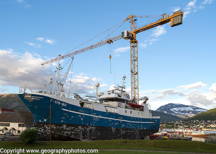 Construction crane towering above fishing boat boat in dry dock, Tromso, Norway