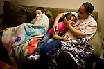 Dennis Sawyer, right, relaxes with his children Isaiah, left, and Frances, center, January 27, 2010 at their home in Sacramento, Calif. The Sawyer family receives $540/month in CalWORKs assistance from the state of California. Dennis is currently unable to work while recovering from cancer, and Sophia hasn't been able to find work. Gov. Arnold Schwarzenegger has proposed eliminating the CalWORKs program in an effort to balance the state's budget. CREDIT: Max Whittaker for The Wall Street Journal.CABUDGET