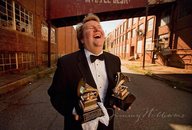 An opera singer holds awards while laughing outside of an old building.