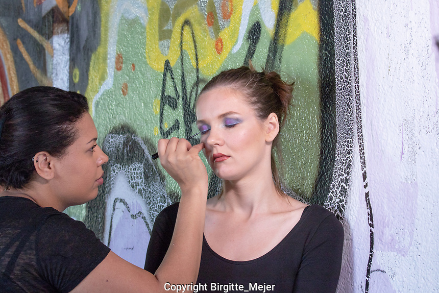 Make-up artist making female model ready for a photo shoot. Model leaning agains a grafiti painted concrete wall, while make-up artist are putting eye shadow on the model. Make-up artist HEAD Salon Jacqueline Silva.