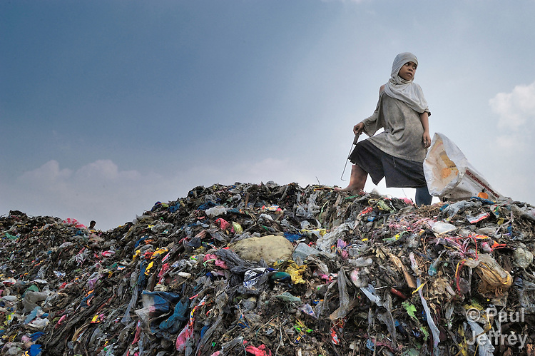 A girl at work scavenging in a garbage dump in Manila, the capital of the Philippines.