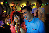 """Jeans factory workers and executives enjoy beers and karaoke in Zhongshan city, China, during the Chinese New Year festival. .This picture is part of a photo and text story on blue jeans production in China by Justin Jin. .China, the """"factory of the world"""", is now also the major producer for blue jeans. To meet production demand, thousands of workers sweat through the night scrubbing, spraying and tearing trousers to create their rugged look. .At dawn, workers bundle the garment off to another factory for packaging and shipping around the world..The workers are among the 200 million migrant labourers criss-crossing China.looking for a better life, at the same time building their country into a.mighty industrial power."""