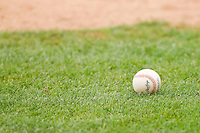 A South Atlantic League baseball sits in the grass behind home plate at L.P. Frans Stadium on May 18, 2011 in Hickory, North Carolina.   Photo by Brian Westerholt / Four Seam Images