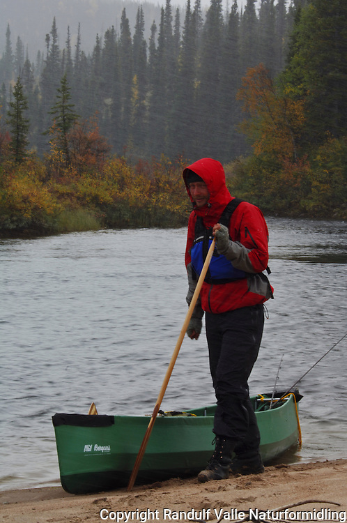 Mann ved kano i regn og sludd ---- Man beside canoe in rain
