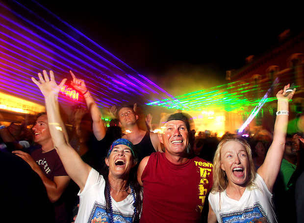 Gina Pfarr of Sioux Falls, S.D., left, Mark Giffen of Springfield, Mo., and Tisa Overman of Milwaukee, Wis., revel in a laser light show with other fun-seekers in downtown Grinnell on July 28 during the fifth night of  RAGBRAI XXXIX.