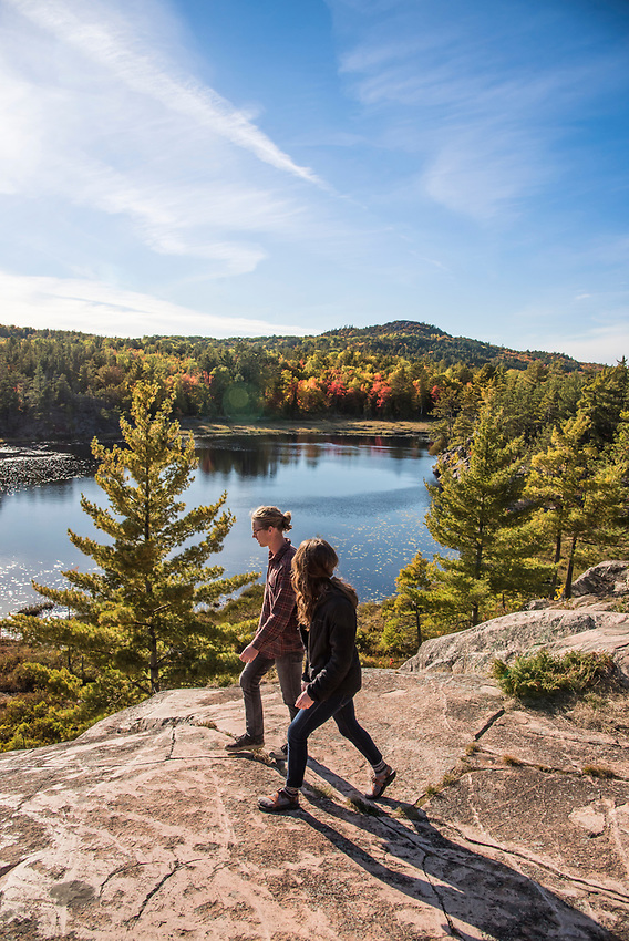 Hikers explore rock outcroppings above Wetmore Pond with Hogback Mountain in the background, near Marquette, Michigan.