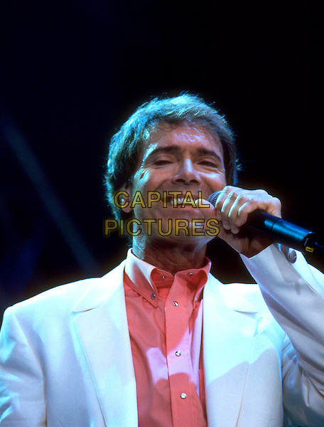 SIR CLIFF RICHARD.Concert in Hyde Park, London,.England, 16th July 1999..portrait headshot white suit coral shirt microphone gig live on stage.CAP/MEL.©Mel Longhurst/Capital Pictures.