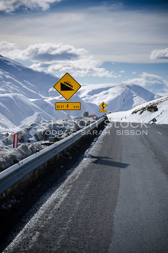 Vertical picture of Steep grade and winding road signs on the treacherous Crown Range road between Queenstown and Wanaka. Winter time, snow and grit on road,  Sunny day looking down Cardona valley.