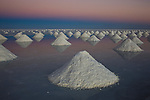 Bolivia, Altiplano, Salar de Uyuni, artificial salt mounts in Salar de Uyuni, largest salt pan in the world; the salt has been shoveled to mounts by salt workers for the salt to dry; sunrise