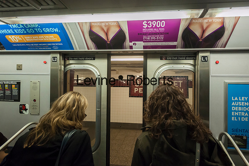 An advertisement for Doctors Plastic Surgery offering breast augmentation in a subway car in New York on Monday, April 7, 2014. The ads feature a full-figured woman offering the surgery at the attractive price of $3900. A number of riders think that the ad is too revealing and objectifies women although it falls within the guidelines of the MTA advertising policies. The MTA is limited in its ability to regulate advertising within its system due to free speech issues and previous lawsuits. The aid is running in 1000 subway cars and 50 stations. (© Richard B. Levine)