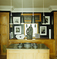 The black walls of the kitchen are covered with black and white photographs