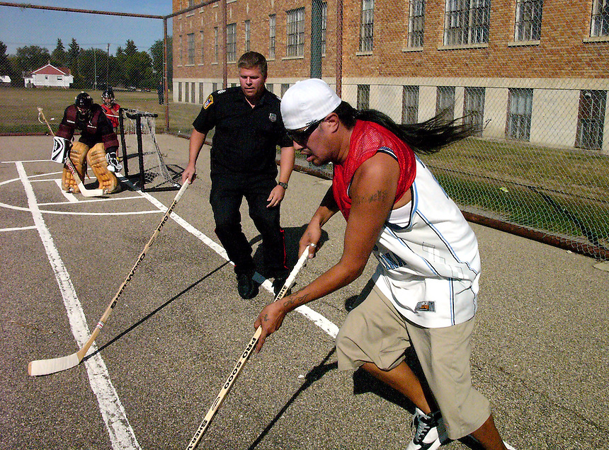 Regina City Police officer Curtis Kemp gets in on a shinny game outside Scott Collegiate during the North Central Community Association's 2007 Fall Fest celebration. MARK TAYLOR GALLERY