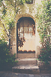 a brown arched door on a quiet street in St Guilhem le Desert, france