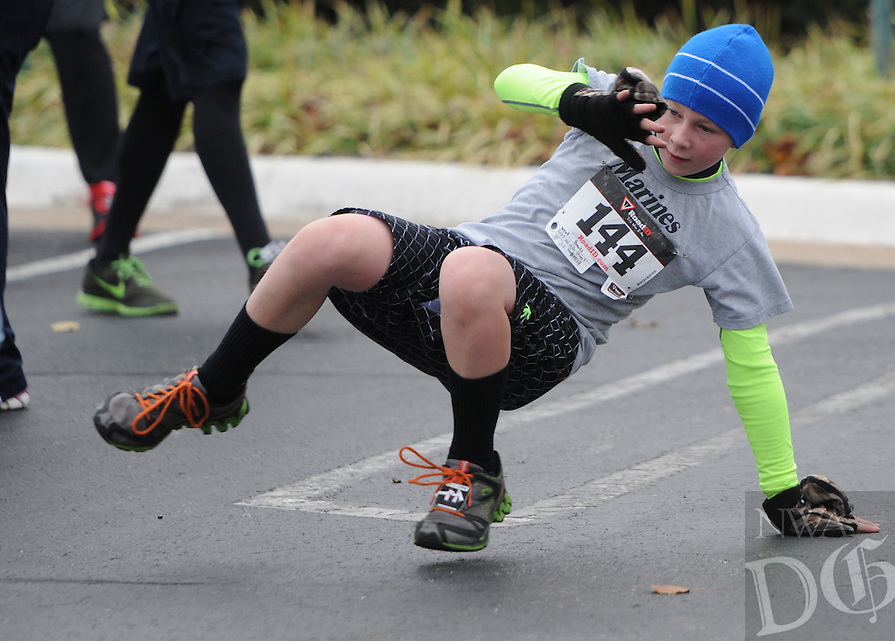 NWA Media/ J.T. Wampler -West Brooks of Rogers busts out some break dancing moves before running in the 7th Annual Turkey Trot 5K Thursday Nov. 27, 2014 hosted by the Sheep Dog Impact Assistance. The event is held each year to raise funds for the program's Christmas Outreach, which provides children of Sheep Dogs (the men and women that make up our nation&rsquo;s military and first responder professions) experiencing financial difficulties with gifts to open for Christmas.<br /> The event helps buy toys, clothing and necessities for children of military members and first responders.