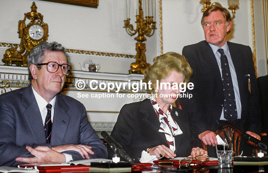 Press conference following signing of Anglo-Irish Agreement by Margaret Thatcher, Prime Minister, UK, and Garret Fitzgerald, Prime Minister, An Taoiseach, Rep of Ireland, at Hillsborough Castle, N Ireland, 15th November 1985. Garret FitzGerald and Margaret Thatcher with Bernard Ingham, British press secretary, keeping a weather eye on the proceedings. 1985111505e.<br />
