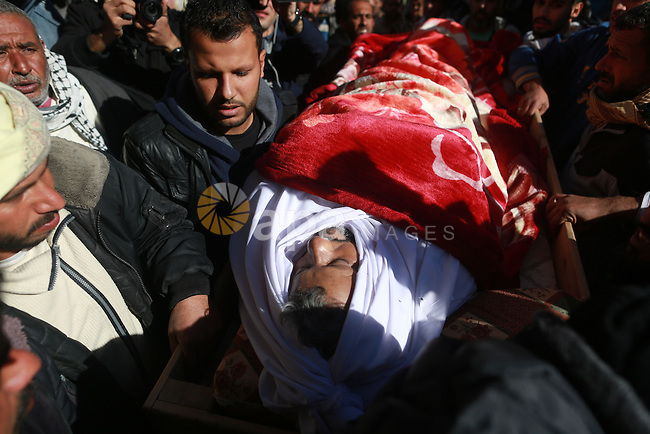 Palestinian mourners carry the body of 48-year-old Yussef al-Buhairi during his funeral in the al-Maghazi refugee camp, located in in the centre of the Gaza Strip, on December 28, 2015. Buhairi who was wounded at the Gaza border during clashes with the Israeli army the previous week died early on December 27 from his injuries, the Gaza health ministry said. Photo by Yasser Qudih