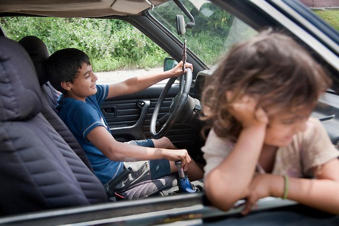 Cantavir, Vojvodina, Serbien, 04.07.2009: Waehrend Andor im Auto seines Onkels spielt und so tut als koenne er selber fahren, hat sich seine Schwester Aniko bereits aus dem Fenster gelehnt und ist bereit f&uuml;r einen kleinen Ausflug mit ihrem Bruder.<br /><br /> <br /> Cantavir, Serbia, 04.07.2009: Andor is pretending to drive his sister in his uncle`s car.