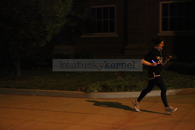 Stacey Martinez runs with her shadow behind her during the first-annual Shadow Run for Fallen Soldiers at UK on Saturday, Nov. 13, 2009.