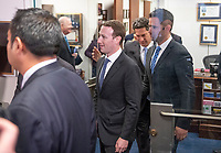 Surrounded by staff and security, Mark Zuckerberg, Co-Founder and Chief Executive Officer of Facebook, walks out of United States Senator Dianne Feinstein's (Democrat of California) office as he makes the rounds on Capitol Hill prior to giving testimony before Congress on Tuesday and Wednesday on Monday, April 9, 2018<br /> CAP/MPI/RS<br /> &copy;RS/MPI/Capital Pictures