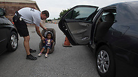 NWA Democrat-Gazette/J.T. WAMPLER Springdale police officer Philip Group sizes a childs car seat for Jasia Lokot, 3, Tuesday Aug. 4, 2015 at Murphy Park in Springdale during the National Night Out. Around 70 car seats were available for residents to have installed for free. The event was part of a national campaign to build trust between police officers and city residents. The event featured free food, music, police and fire vehicles on display, contests and a movie. The Springdale police department joined more than 16,000 law agencies nationwide to participate in the campaign.<br />