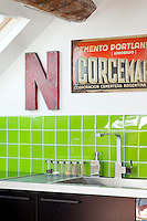 A splashback of lime-green tiles introduces a fresh and cool note to the kitchen