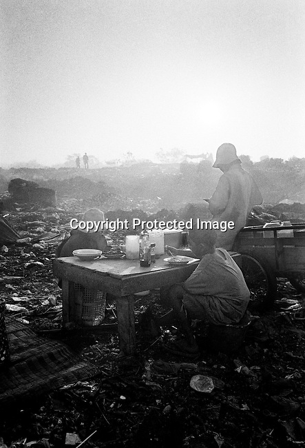 Unidentified children eat at a garbage dump on March 11, 1998 at the Stung Meanchey garbage dump outside Phnom Penh, Cambodia. Hundreds of children aged 4-7 years old work in bad conditions making about $1 per day. Many families come from the Cambodian countryside looking for work and food. (Photo by: Per-Anders Pettersson)