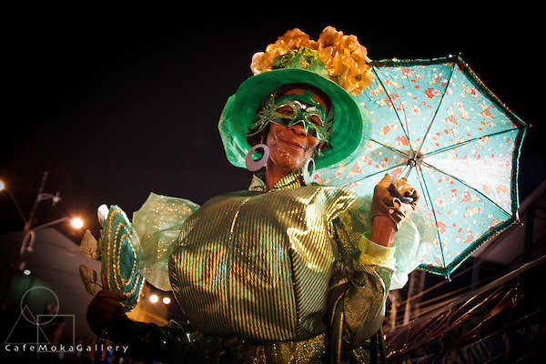 Traditional mas - Dames Lorraine 'Madame Big Shot' in green with a blue paraso, hat with gold flowers and mask -  Nelly Joseph