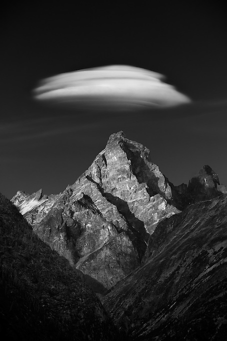 A lenticular cloud forms over this unnamed jagged peak in the late afternoon.