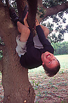 A1X0T1 Teenage boy hanging out of a tree