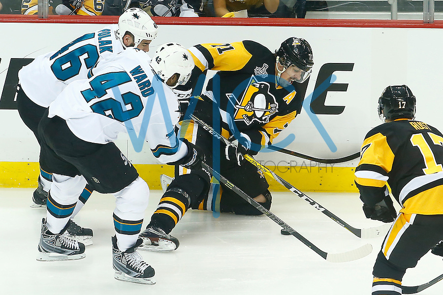 Evgeni Malkin #71 of the Pittsburgh Penguins reaches for the puck from his knees along the boards in front of Roman Polak #46 and Joel Ward #42 of the San Jose Sharks during game two of the Stanley Cup Final at Consol Energy Center in Pittsburgh, Pennslyvania on June 1, 2016. (Photo by Jared Wickerham / DKPS)