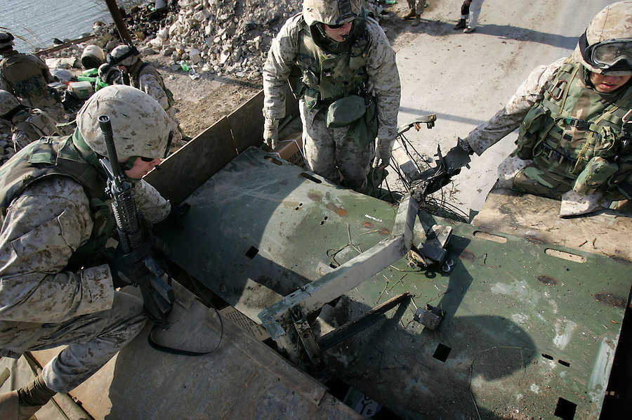 During a recovery mission, Marines from Fox Company 2nd Battalion 5th Marines load a 200 lbs. fragment of a Humvee tossed 100 meters through the air and into a canal by the detonation of an IED into to the rear of another vehicle in Ramadi, Iraq on January 3, 2004.