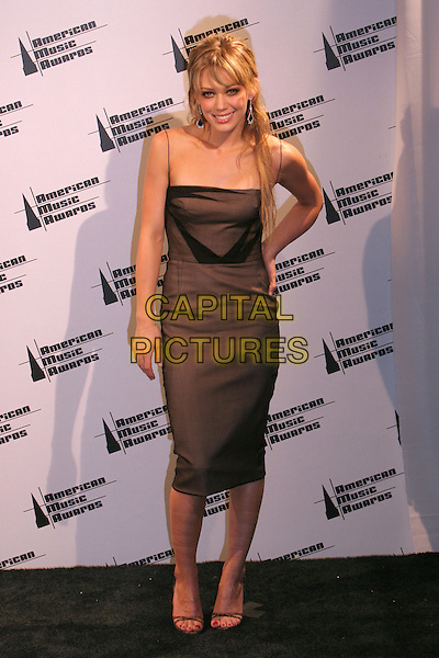 HILARY DUFF.33rd Annual American Music Awards - Press Room held at the Shrine Auditorium. Los Angeles, California..USA, United States..22nd November 2005 .Ref:ADM/ZL.full length brown strappy spagetti straps dress wavy curly tousled hair long fringe smiling hand on hip.www.capitalpictures.com.sales@capitalpictures.com.© Capital Pictures.