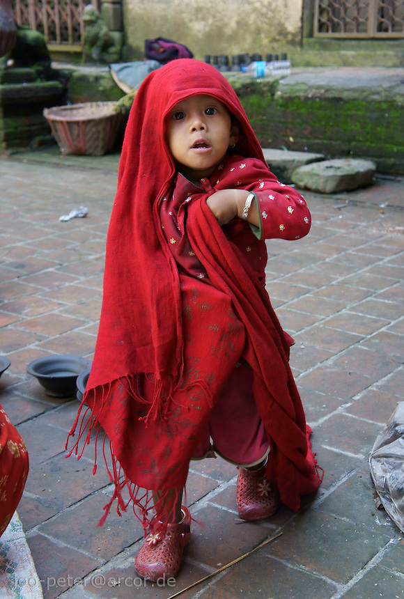 child of pottery craftsmen in playfull mood in Bhaktapur, Nepal, pulling a red blanket over his head