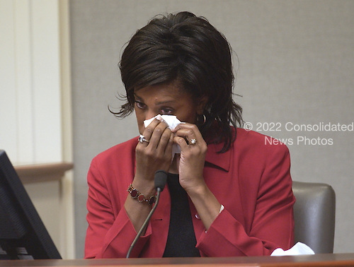 Witness Tanya Brown, the aunt of sniper victim Iran Brown, wipes her eyes as she testifies during the trial of sniper suspect John Allen Muhammad in courtroom 10 at the Virginia Beach Circuit Court in Virginia Beach, Virginia on October 29, 2003.  Brown dropped her nephew off at the Benjamin Tasker Middle School in Bowie, Maryland the day he was shot. <br /> Credit: Dave Ellis - Pool via CNP